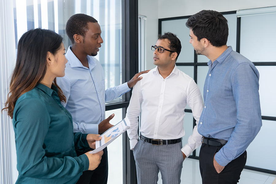 Four young business people discussing negotiation strategy