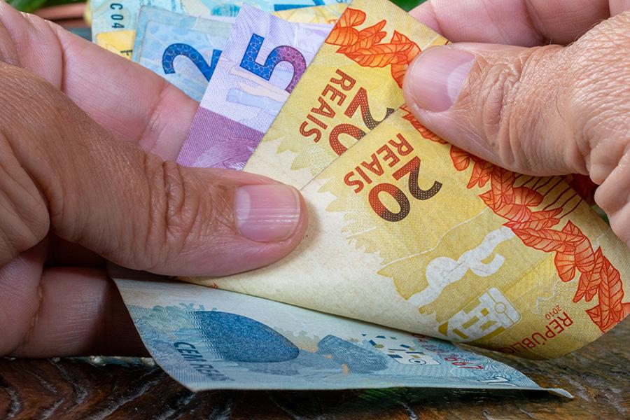 hand of man counting Brazilian money