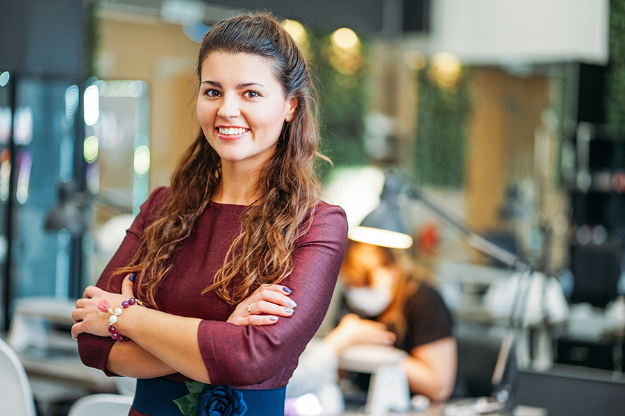 Young charming smiling woman owner of beauty salon nail bar, concept of own small business