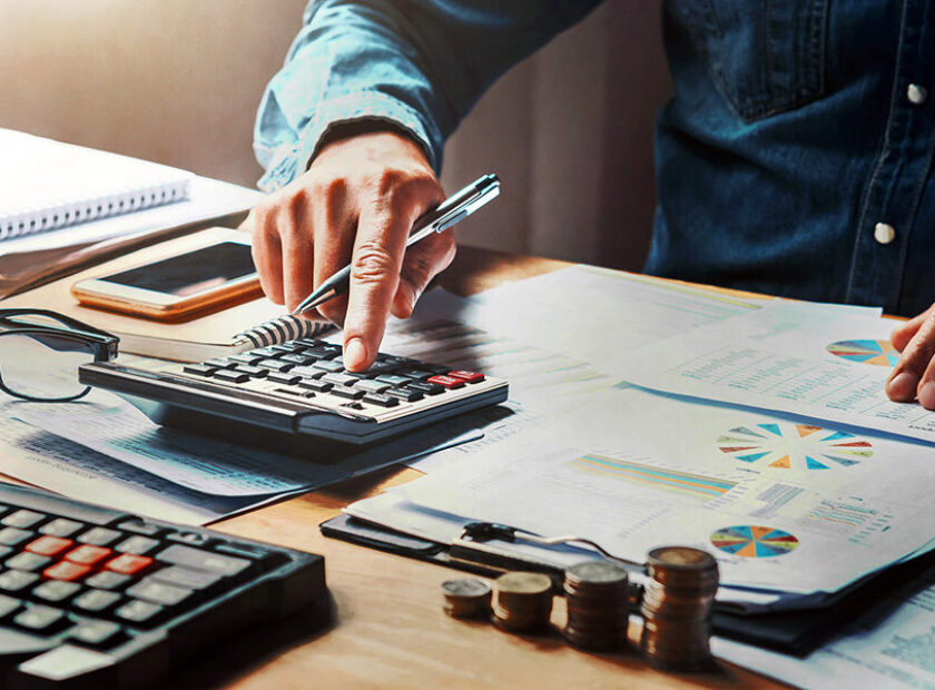 businessman using calculator with hand holding pen working in of