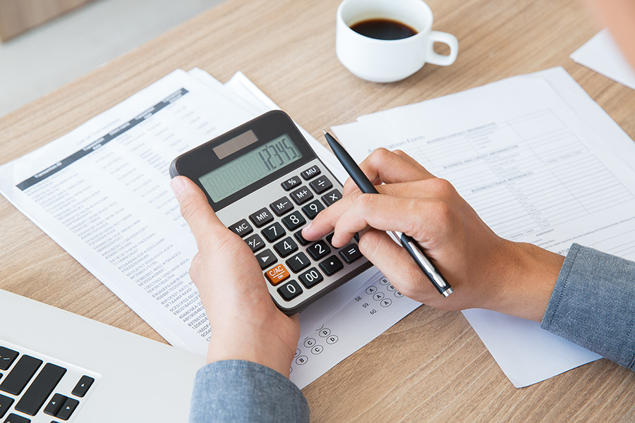 Man using calculator to count income and outcome