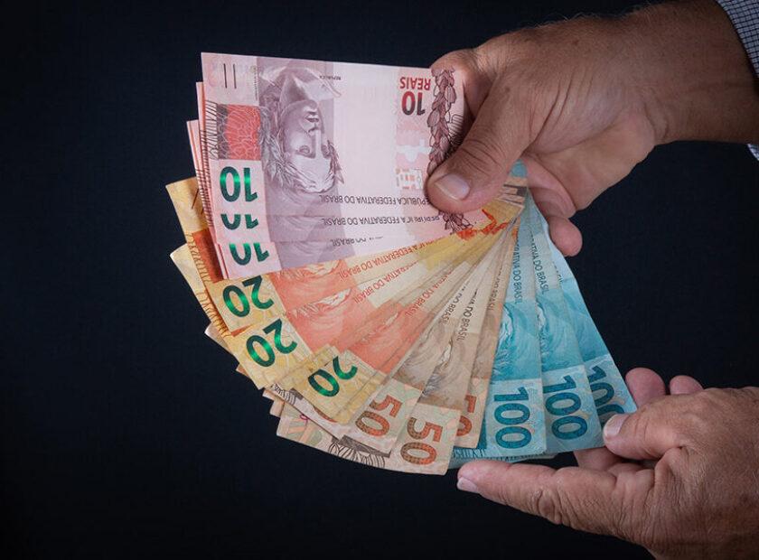 Man holding Brazilian money banknotes Finance concept