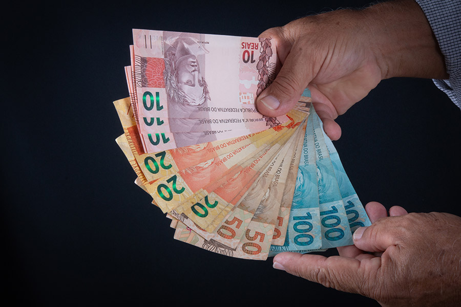 Man holding Brazilian money banknotes Finance concept