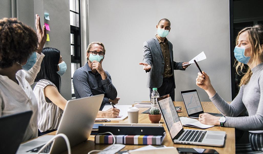 Business people wearing masks in coronavirus meeting, the new no
