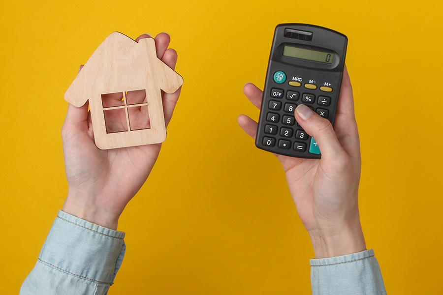 Calculation of the cost of housing, rent. Female hand uses calculator and hold house figure on yellow background. Top view