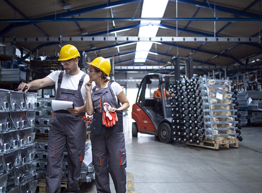 Factory workers checking quality of products in industrial wareh