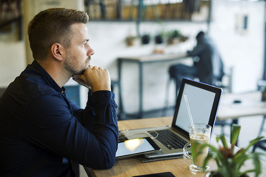 Young businessman sitting in cafe bar with laptop being worried