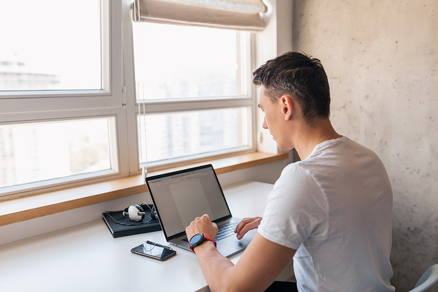 young handsome man in casual outfit sitting at table working on laptop, freelancer at home, view from back