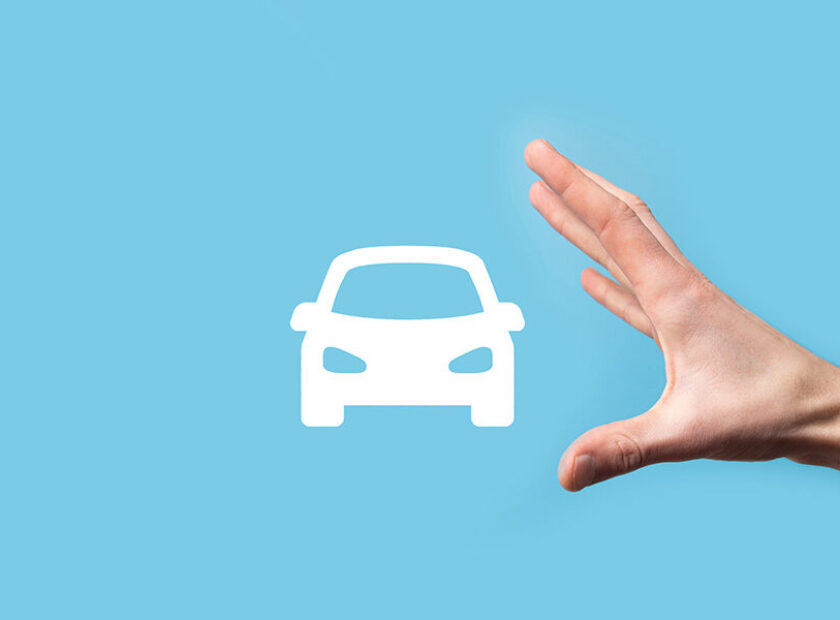 Male hand holding car auto icon on blue background. Wide banner composition.Car automobile insurance and collision damage waiver concepts