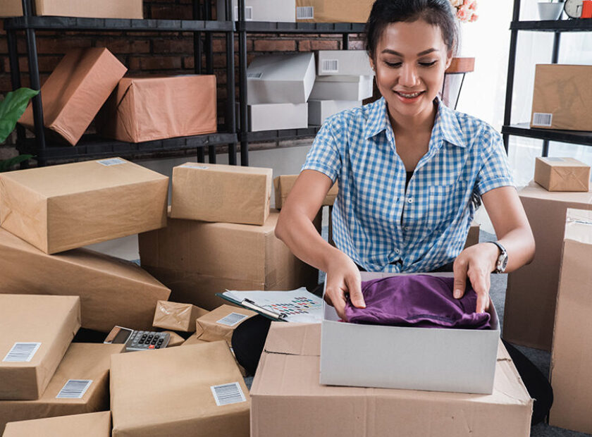 Young woman packing of clothes put on the boxes