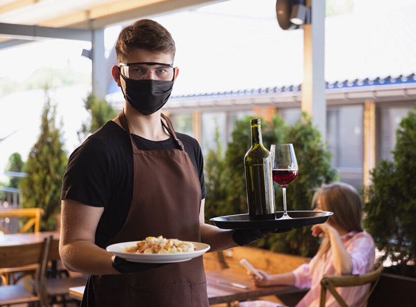 The waiter works in a restaurant in a medical mask, gloves during coronavirus pandemic