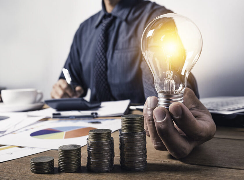 Business man holding a light bulb with coins money and copy spac
