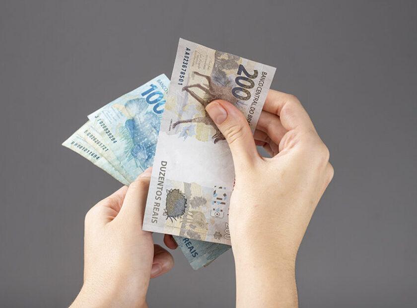 woman hand holding Brazilian money notes. Reais.