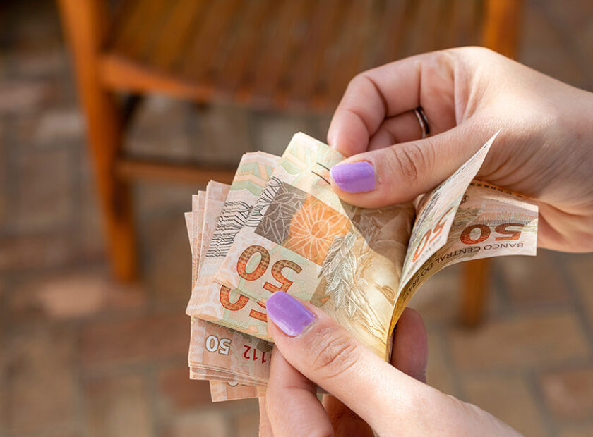 woman hand providing Brazilian money banknotes