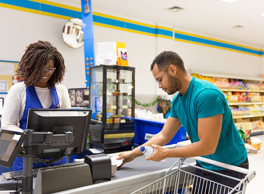 Female cashier reading barcodes at cash register