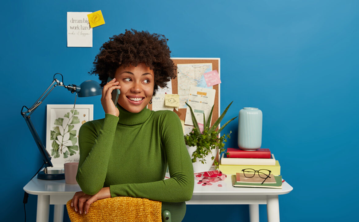 Afro American woman talks via smart phone, works at desk in home office, has cheerful face expression, dressed in casual wear, poses against desktop, isolated over blue wall with sticky notes