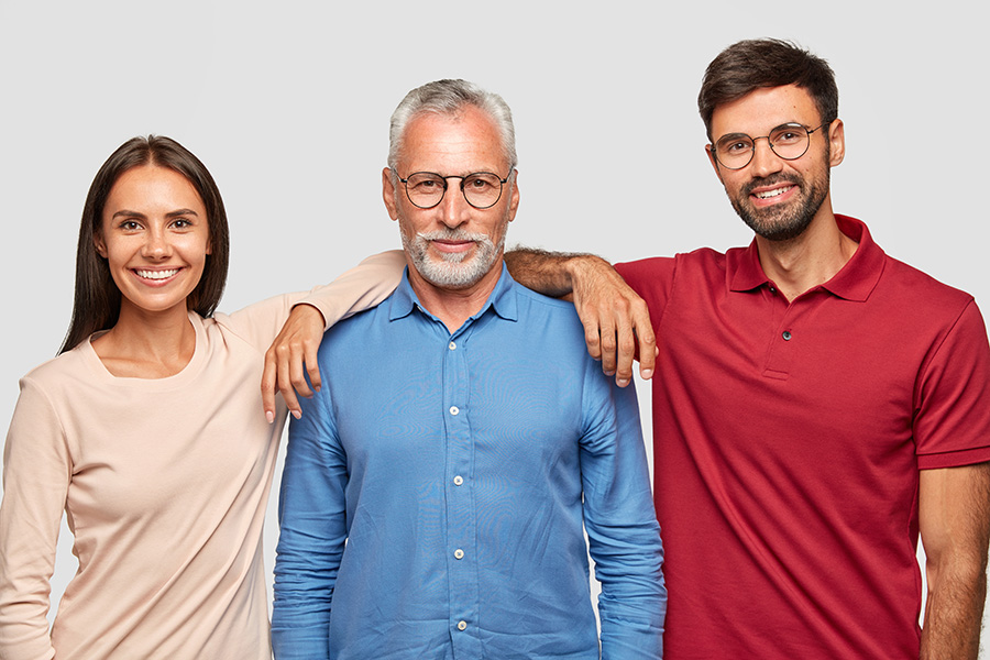 Multi generation concept. Family portrait of mature wrinkled man dressed in stylish shirt, stands between his daughter and son who came to congratulate him with anniversary, have good relationships