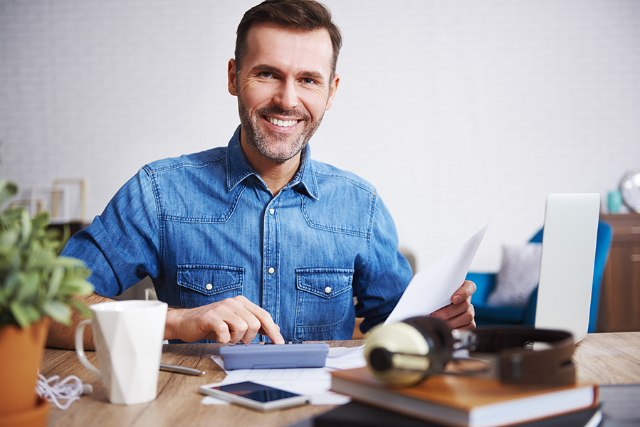 Portrait of smiling man calculating his monthly expenses