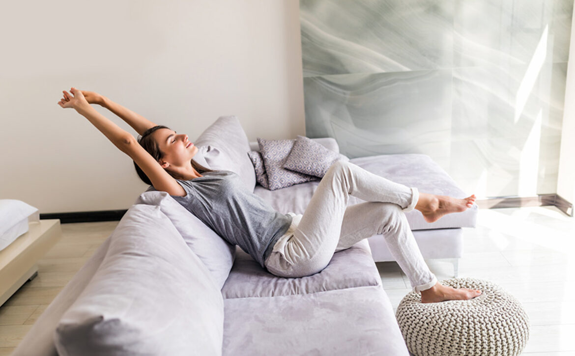 Smiling young woman relax lying on couch